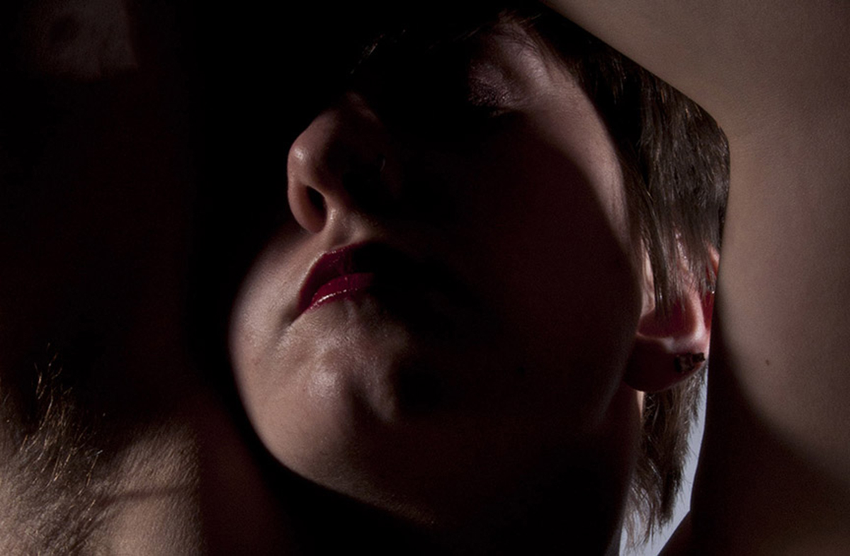 A close up low-lit image of a person taken from below. The lighting highlights their chin, lips, and nose, and their arms and long armpit hair. Their arms are raised over their head, with one arm holding the other. Their eyes are closed and their eyes are in shadow. They are wearing bright red lipstick, and they have light skin and short brown hair.