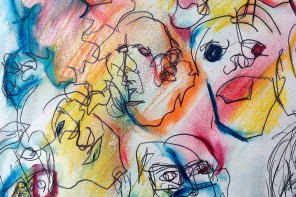 A pen and pastel drawing on white paper of caricatured and loosely drawn faces. The faces are defined in black pen, while blue, orange, pink, red, yellow and green pastel is smeared between and around the outlines. The texture of the paper is visible.