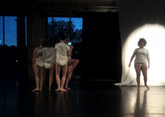 Live performance documentation. In a dimly lit room with a black floor and veiled dark blue windows, four dancers in white t-shirts and diapers stand in a cluster, mostly with their backs to the camera, while another dancer facing forward, is semi illuminated by a spotlight on a white sheet behind them.