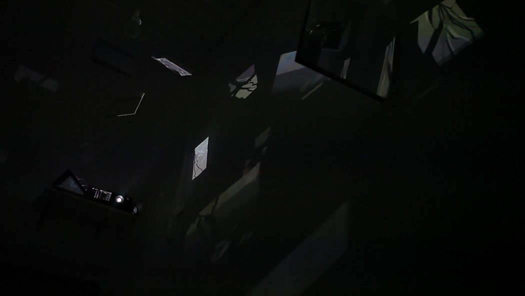 Installation view. In a completely blackened room, shards of light and the contours of a projector are visible. The light shards make various geometric shapes on surfaces in the room, none are distinct.