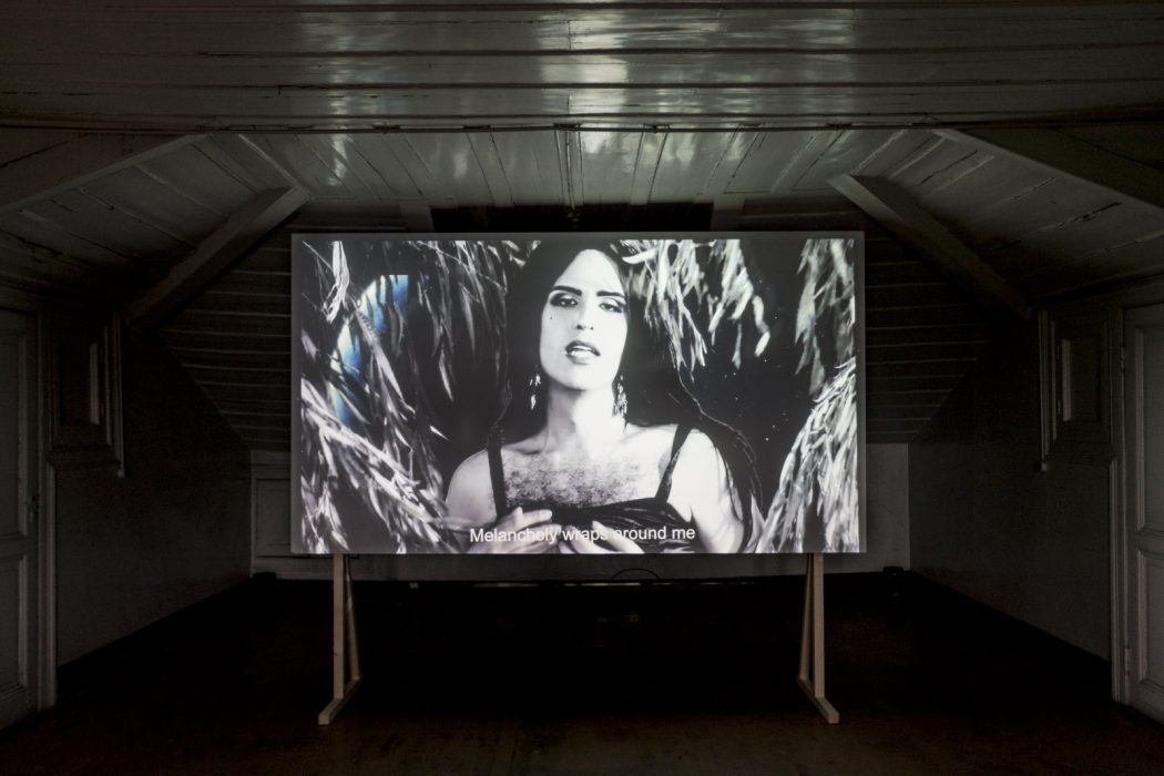"""Installation view. In the center of a dark room, a black and white video is projected onto a screen. In the video, a person is standing amongst tree branches with long skinny leaves. The person has their hair down, bold makeup outlining their eyebrows, eyes, and lips. They're wearing a black strappy top, and some dark chest hair is visible. A line of subtitles overlays their hands in front of their chest reading """"Melancholy wraps around me""""."""
