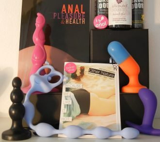 "A tableau of books, blocks, anal toys, plugs, beads and lube are arranged against a wall. One book has a view of someone's bare behind with the title ""ANAL PLEASURE & HEALTH"" visible. Another title reads ""BECAUSE WE LIKE IT HOT"" overlaid on a book cover of someone's thighs, butt, and torso in a top and underwear. Above a block, a pink pin stating ""I [graphic of a butt plug] anal"" rests against a bottle of lube."