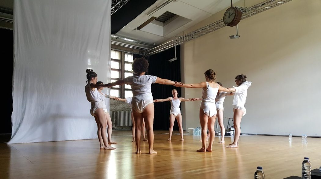 In the center, a group of eight people stand in a circle holding each other's arms/wrists outstretched in a naturally lit rehearsal/dance studio. They are all barefoot and wearing loose white underwear briefs, in addition to varying white tops (tanks, tees, hoodie). There is a large white fabric hanging loosely from the ceiling onto the floor behind and to the left of the performers.