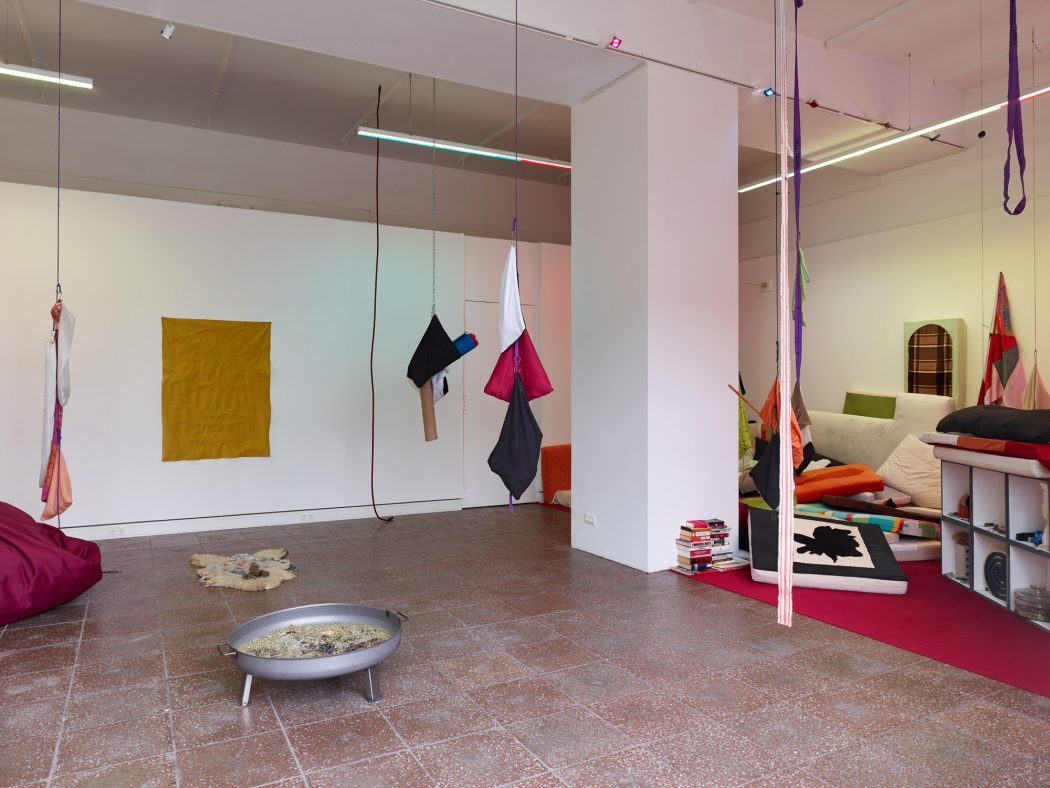 Installation view of a room with varying brightly-colored soft artworks suspended from the ceiling via thin cord or string. In the center, a square column, to the right, a low, freestanding set of shelves with various objects, and piles of pillows. In the foreground, to the left of the column, a freestanding metal fire pit, contents unknown.