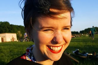 Full-framed portrait of a woman with brown hair and red lipstick standing outside in the sun. She is smiling big and her eyes are squinting. In the background, there is a clear blue sky and folks hanging out recreationally on a grassy field with trees in the distance.