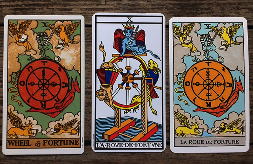 Three Wheel of Fortune tarot cards next to each other on a medium wood surface. The wheel in the first is red with clouds around it, the wheel on the second has dragons on a moving wheel, and the third has orange with a sky in the background.