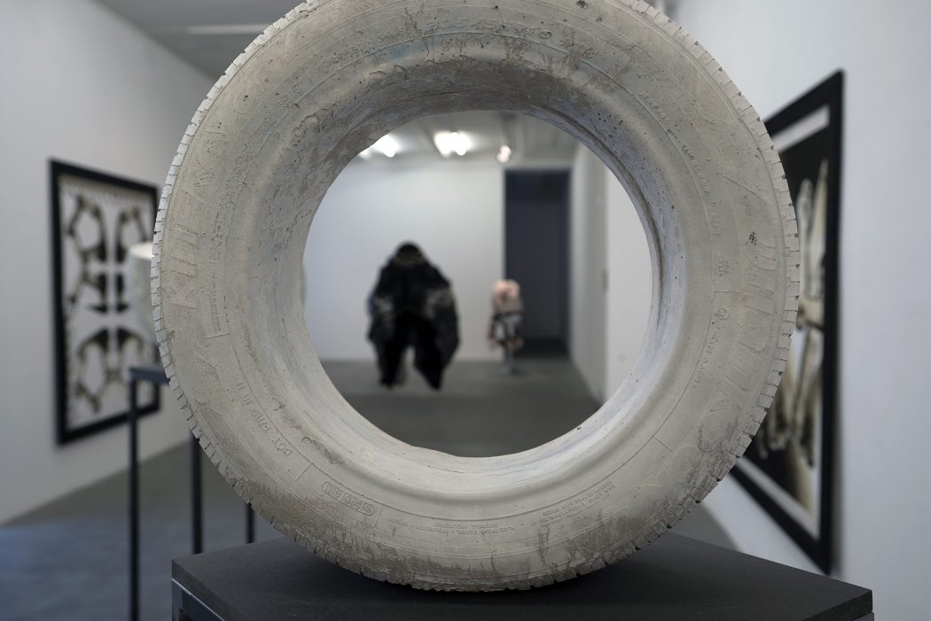 An image of installed art. A cement tire sculpture is visible in the foreground, and other artwork can be seen through the center and around the sides of the sculpture.