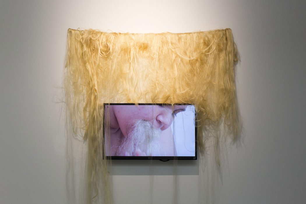 A digital screen with a still from nicola awang's video, depicting a black woman eating blonde hair extensions. On the wall behind the screen, blonde hair extensions are draped.