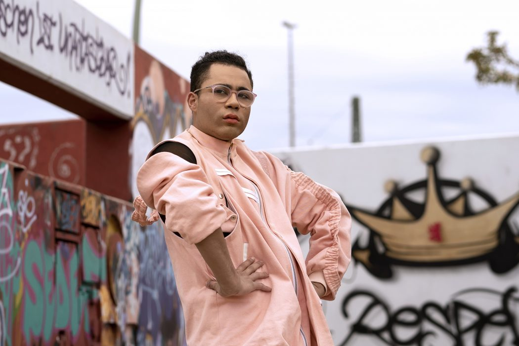 A waist-up picture of a person standing in front of of graffiti'd walls. They have brown skin, dark hair, are wearing glasses, and are looking at the camera, unsmiling. They are wearing a pink outfit with white accents and a black bodysuit underneath.