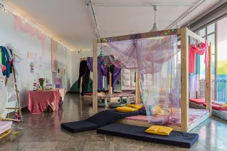 Installation view of Bedtime at Arsenal Gallery. A four poster bed of raw wood is in the middle right of the frame, and sitting pads and pillows spill off the bed into the foreground. There are tables and a view of the gallery walls, with writing and gauze on them. The scene is lit with natural light.