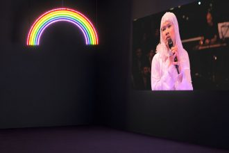 An image of a dark room with grey walls and a purple carpet floor. On the left side of the frame, a glowing LED rainbow hangs down from the ceiling. On the right, a screen with a person in a blonde wig and white outfit using a handheld microphone looks out at the room.