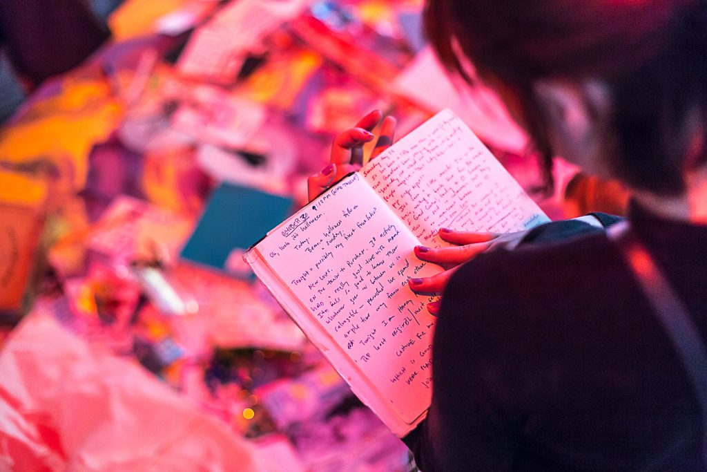 A person reading a handwritten notebook. The photo is taken over their shoulder and is pink-toned.