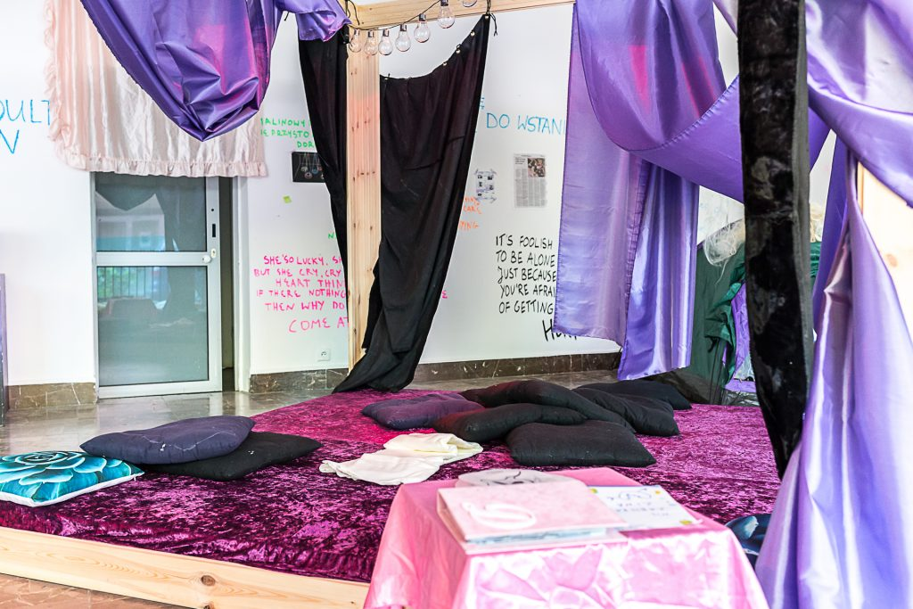 A bed with cushions and drapes, looking toward a wall. The hangings are pink and purple.