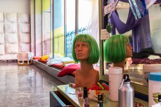 A mannequin head with a green wig, a mirror and makeup.