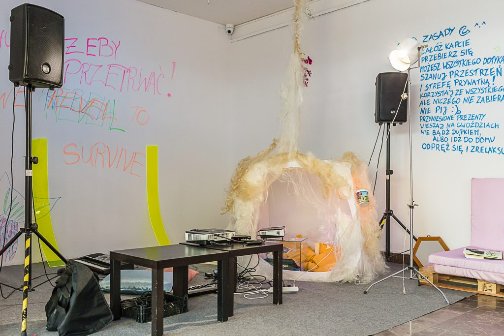A picture of an audiovisual setup in the exhibition. There is writing on the wall and a tent covered in hair.