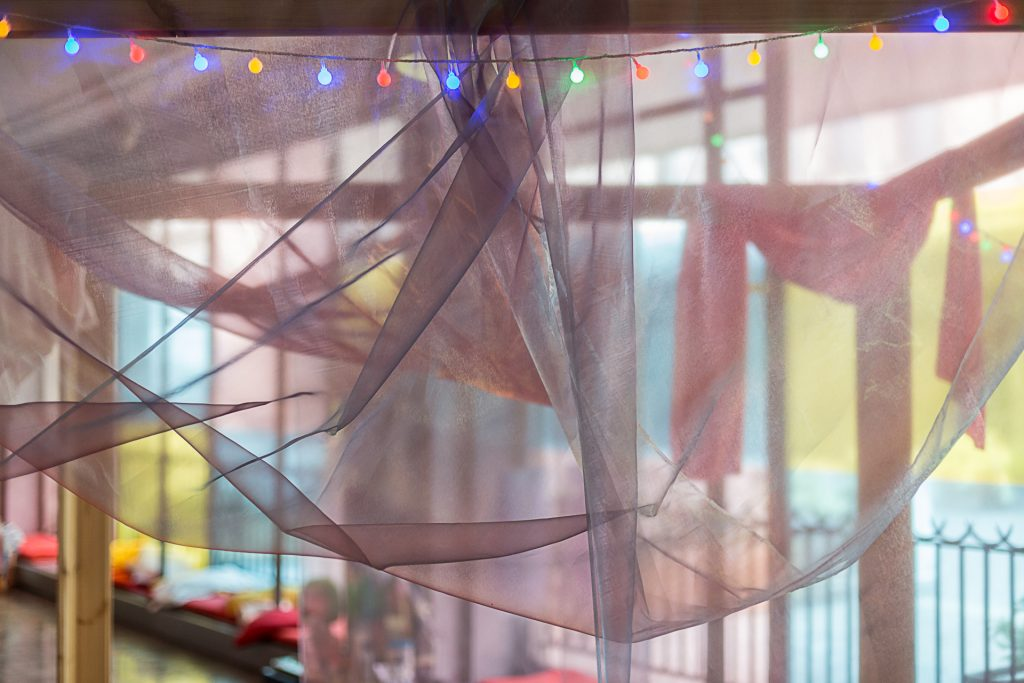 A close up photo of a purple gauzy bed-hanging, with colored lights along the top.