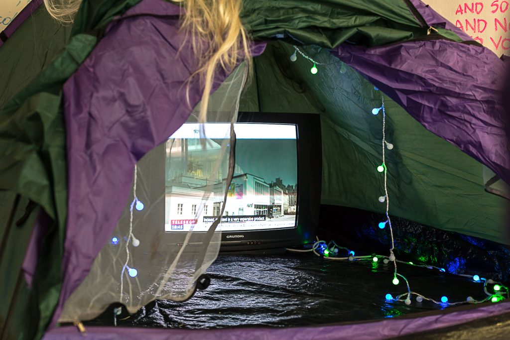 A photo of the opening of a tent with a video screen in it. There are lights around the edge.