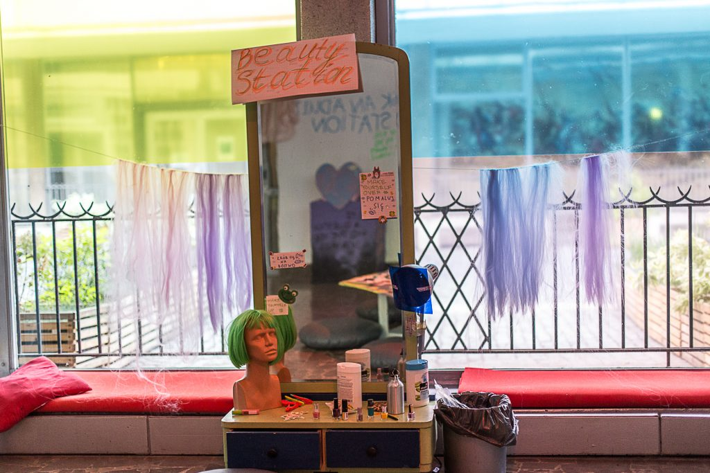 A makeup table with windows covered in colored plastic behind. The table has nail polish, makeup and a mannequin with a green wig on it.