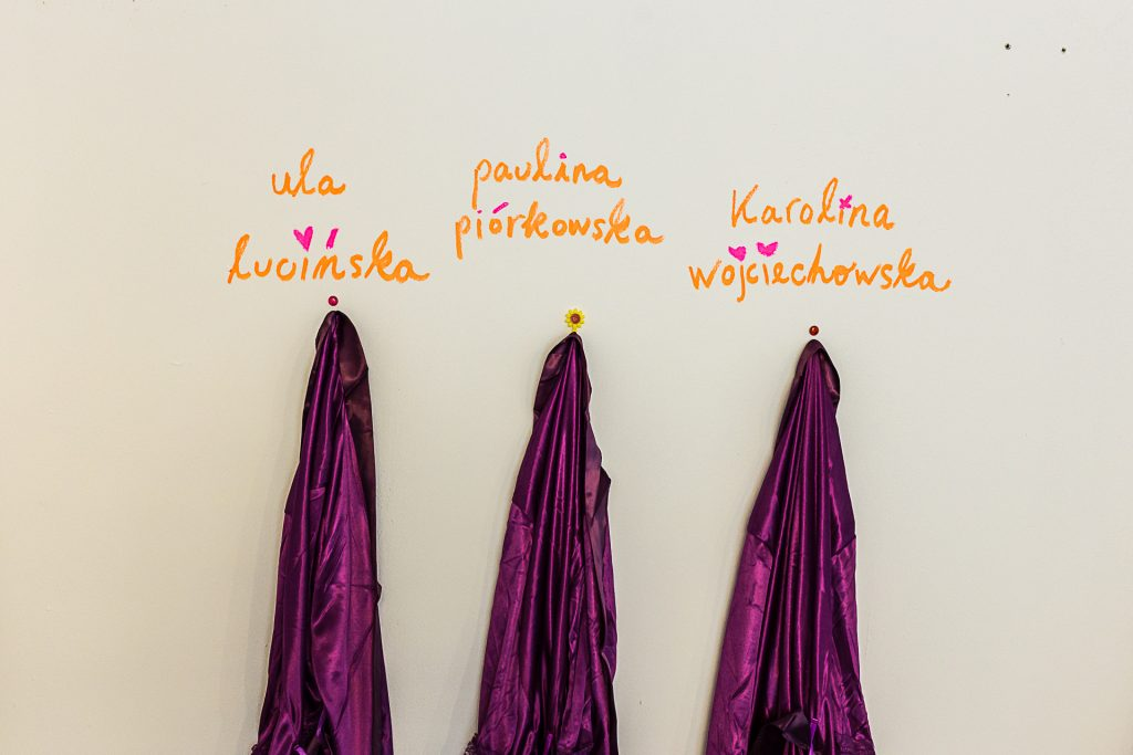 Three purple silky robes hung on the wall under the names of the girlhood members.