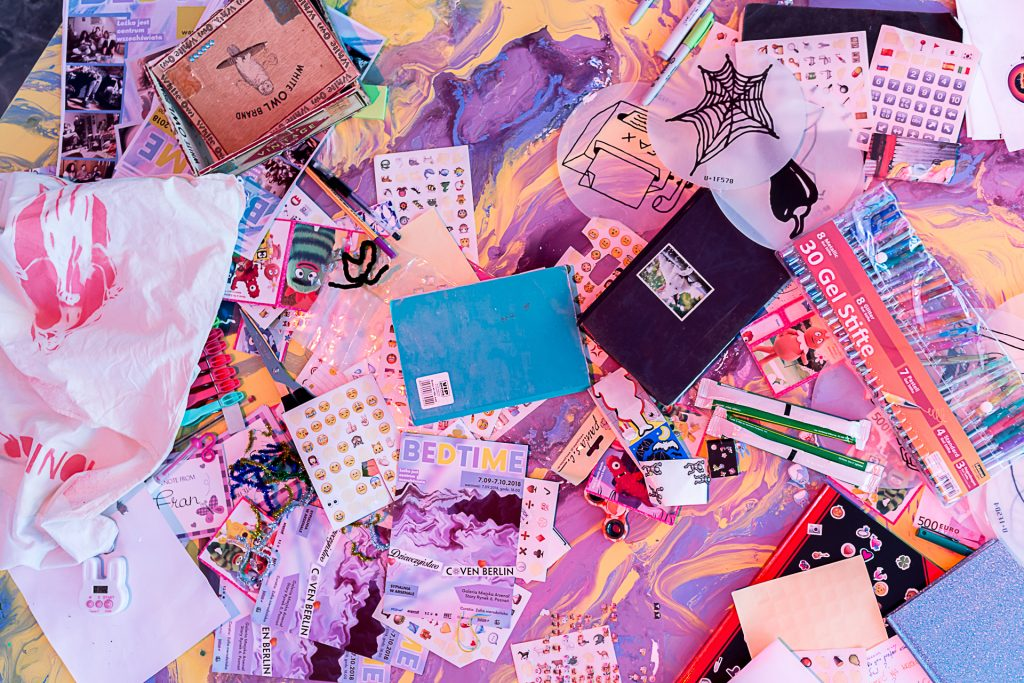 A table covered in stickers, notebooks, journals, pens, and other stationary supplies. The color scheme is mostly pink and purple.