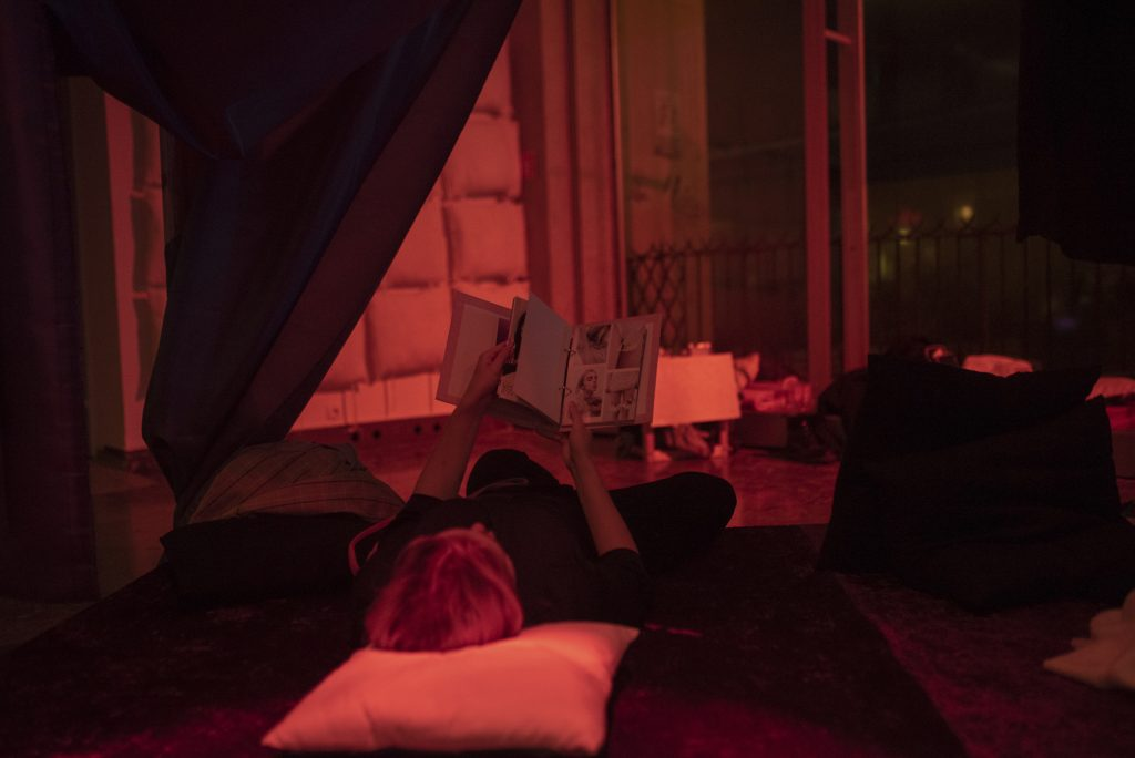 Someone reading a book on the bed. The photo is dimly lit.