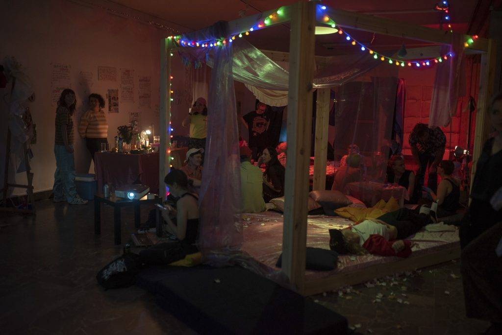 A picture of a darkened room. There is a bed with lights hanging from it, and lots of people hanging out. There is a party atmosphere.