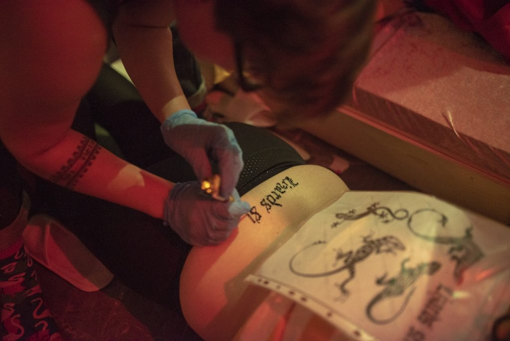 A person wearing gloves and drawing a design on the lower back of another person. A guide sheet lays on their back.