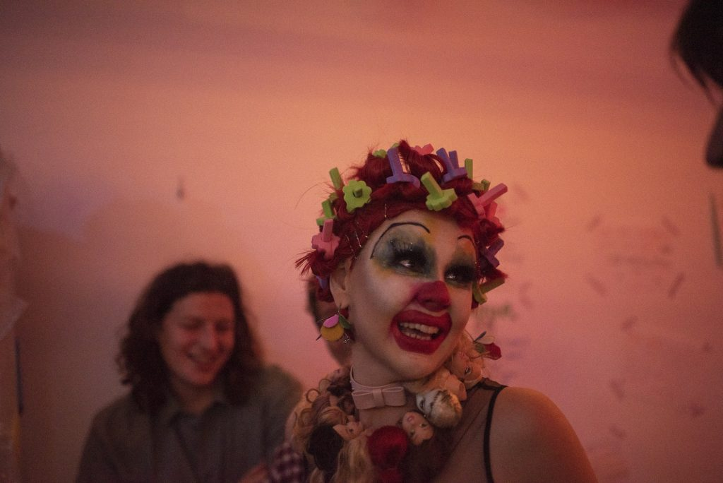 A person wearing clown makeup looking to the right of the camera.