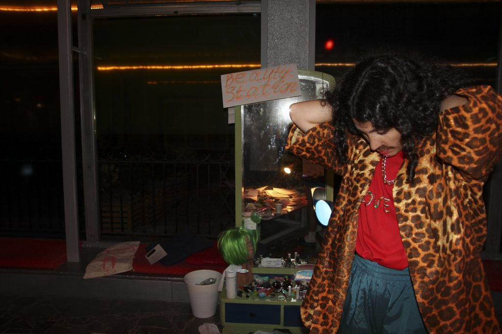A person wearing a leopard print jacked and bright colored clothing. It is a high contrast image.