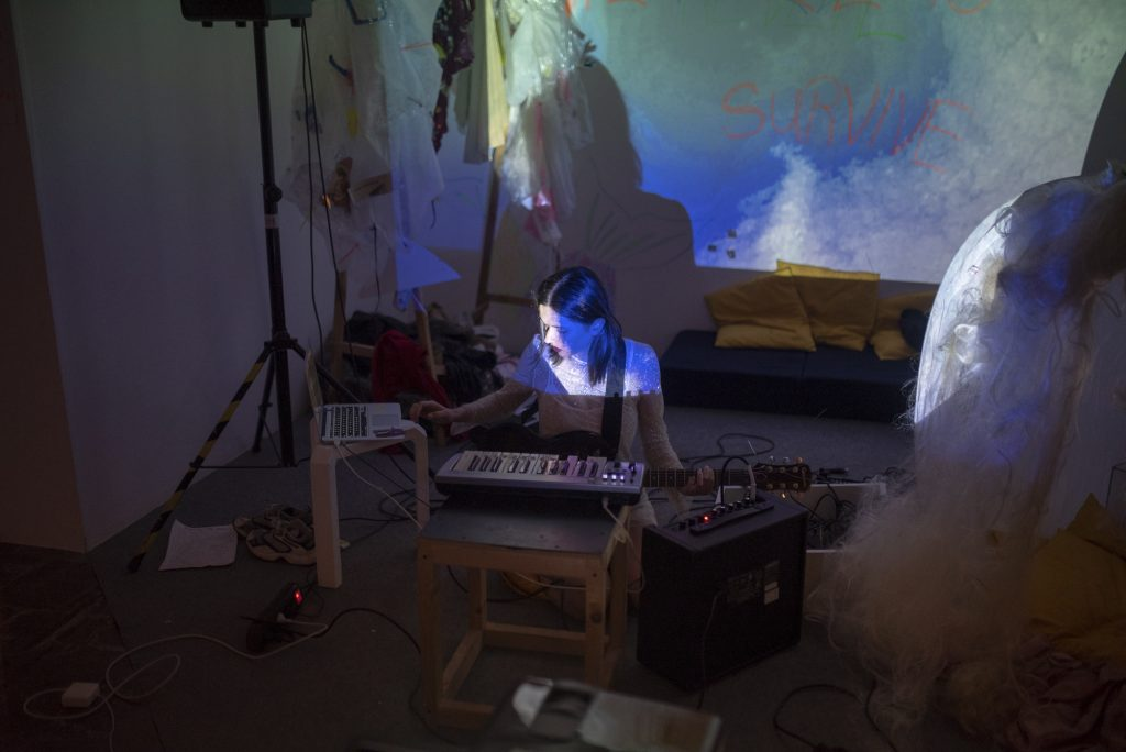 A person holding a guitar in front of a computer. They are bathed in the blue light of a projector.