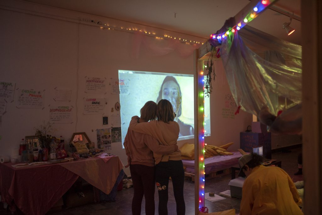 Two people with their arms around one another watching someone on a projector.