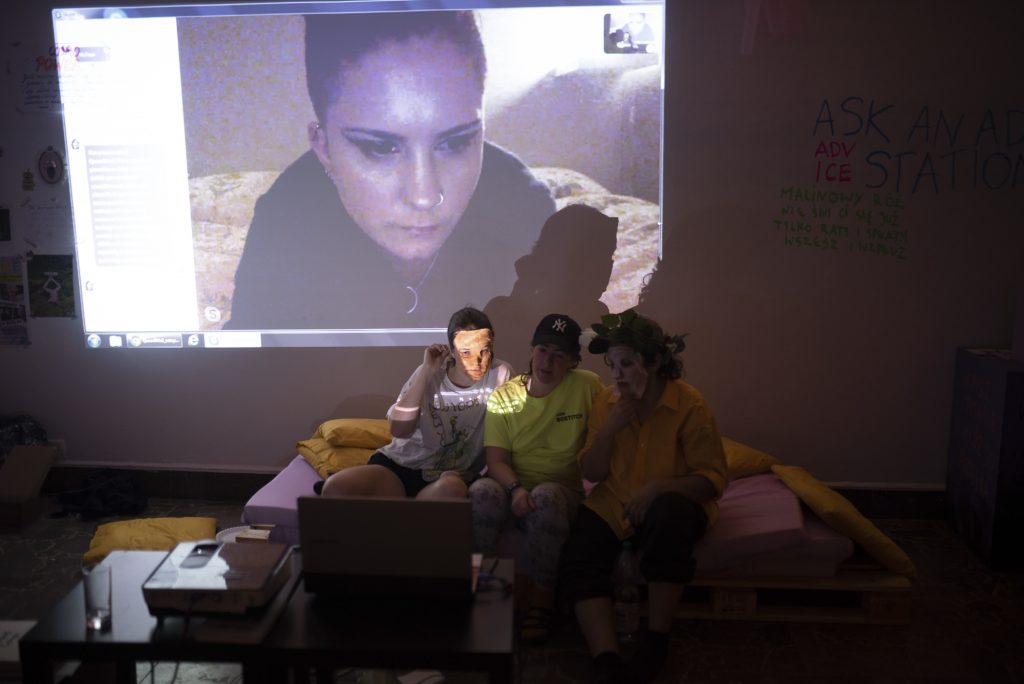 Three people sitting on a bed with a person on skype projected over them.