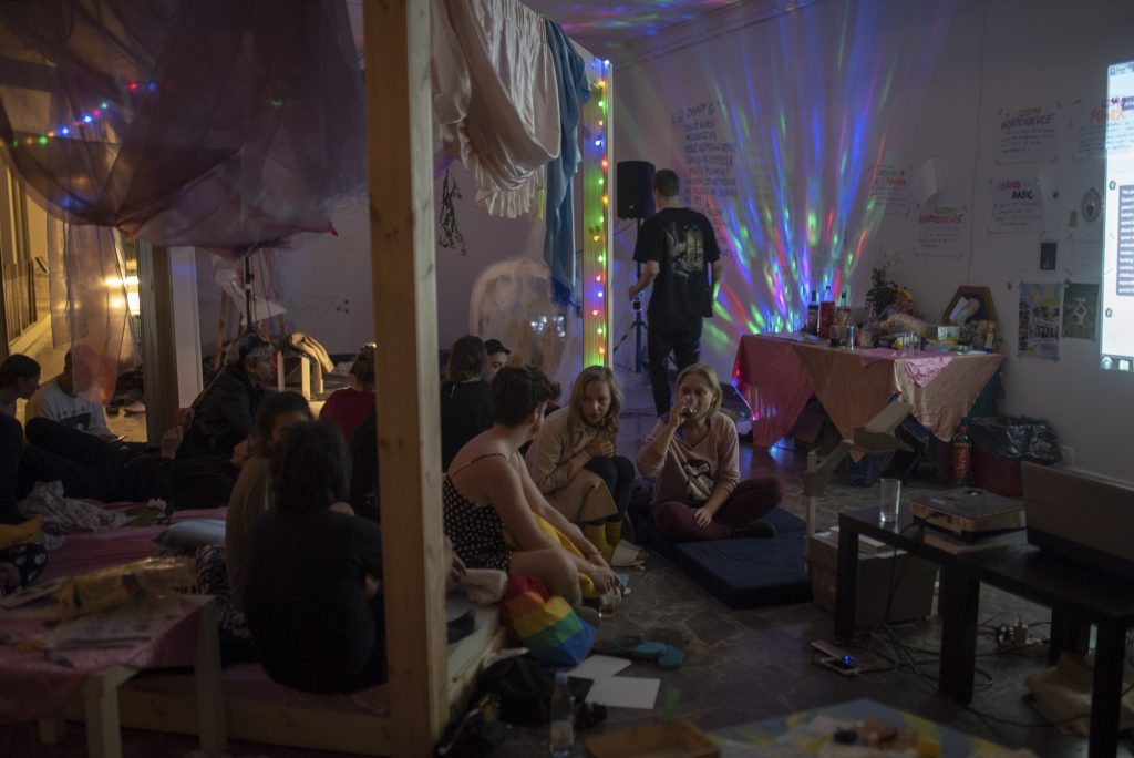A scene with a bed and a bunch of people sitting on it. The scene is bathed in rainbow LED light.
