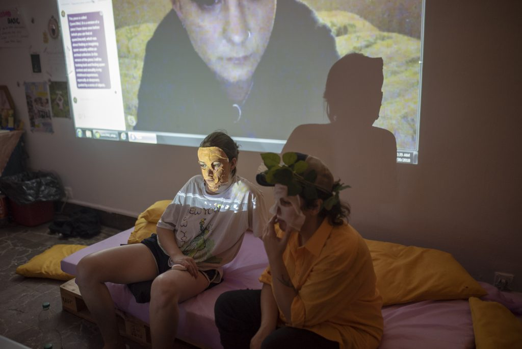 Two people sitting on a bed looking at someone on skype, who is projected behind them.