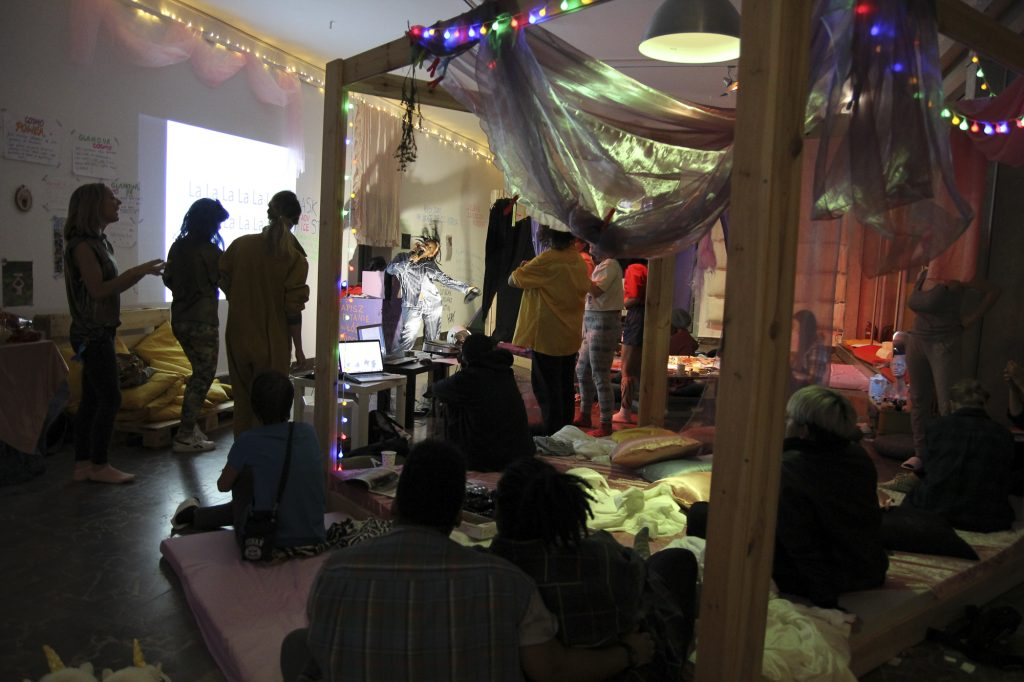 A bunch of people sitting on a bed. There is a projector on in the background.