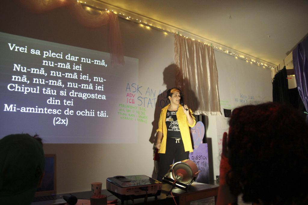A person standing next to a projected set of song lyrics.