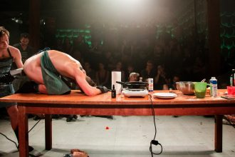 Live performance documentation. The room is dark except for a flood lighting that illuminates a large wooden table, whose left side is strewn with various kitchen implements (hot plate, saute pan, tableware) and baking ingredients and the two nude performers wearing green aprons and black surgical gloves. One person is on top of the left side of the table, knees bent, hunched over with their arms above their head, while the other person is standing behind them on the floor, penetrating their asshole with an implement. In the dim background, three tiers of bleacher style seating show a packed audience of spectators.