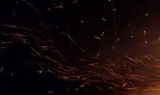 sparks from a fire fly through dark night air