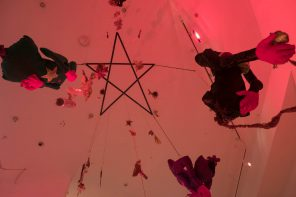 A picture facing up toward the ceiling, which has a pentagram on it. Hanging down from the pentagram are fabric figures, herbs, and other objects.