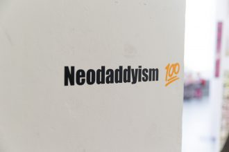 neodaddyism 100 title on white wall, neodaddyism in black text with 100 in orange