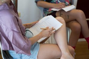 A photograph of a light skinned person. The photo is from the right side at about shoulder level, and the person's legs are crossed, with one ankle on the knee. The person is using their thigh to write on a questionnaire paper. They are wearing a purple satin shirt and light blue jean cutoffs.