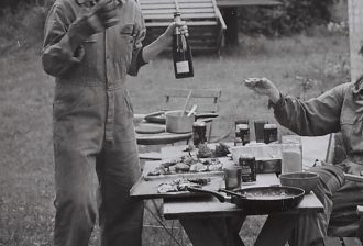 A black and white photograph of two people wearing work jumpsuits. One is standing and holding a bottle of sparkling wine, while the other is reaching for it from the right side of the frame. Neither person's head is visible. The table between is laid with food and dirty plates. They are outside in a grassy, possibly forest area.