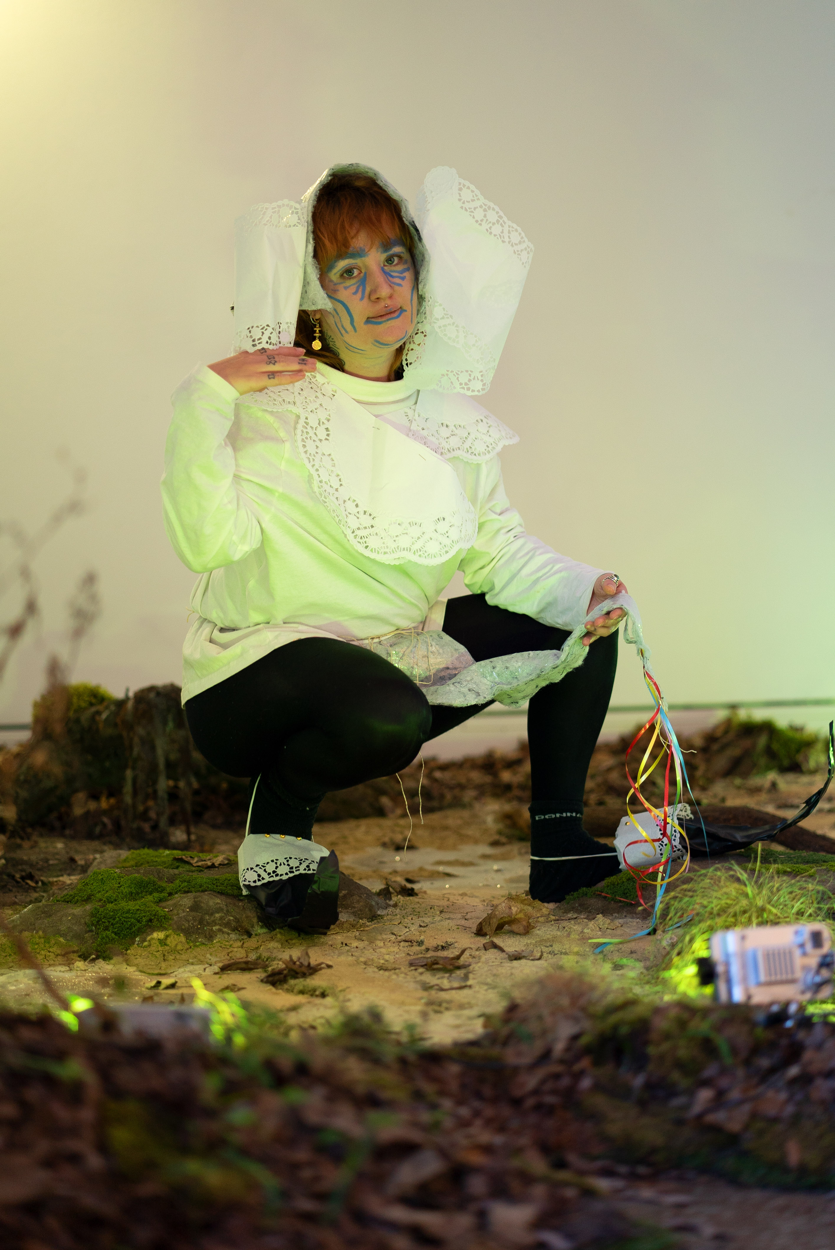 The photo shows a person posing in a squatting position. They are wearing a headdress and a top made of white lace, black leggings and homemade goblin shoes made of black gaffer and white lace. They have put their right hand on the right shoulder and look directly into the camera. The person's body is illuminated by a green light on the ground. The ground is an artificial swamp, which consists of soil, moss, dried leaves and grass. The background is a white wall.