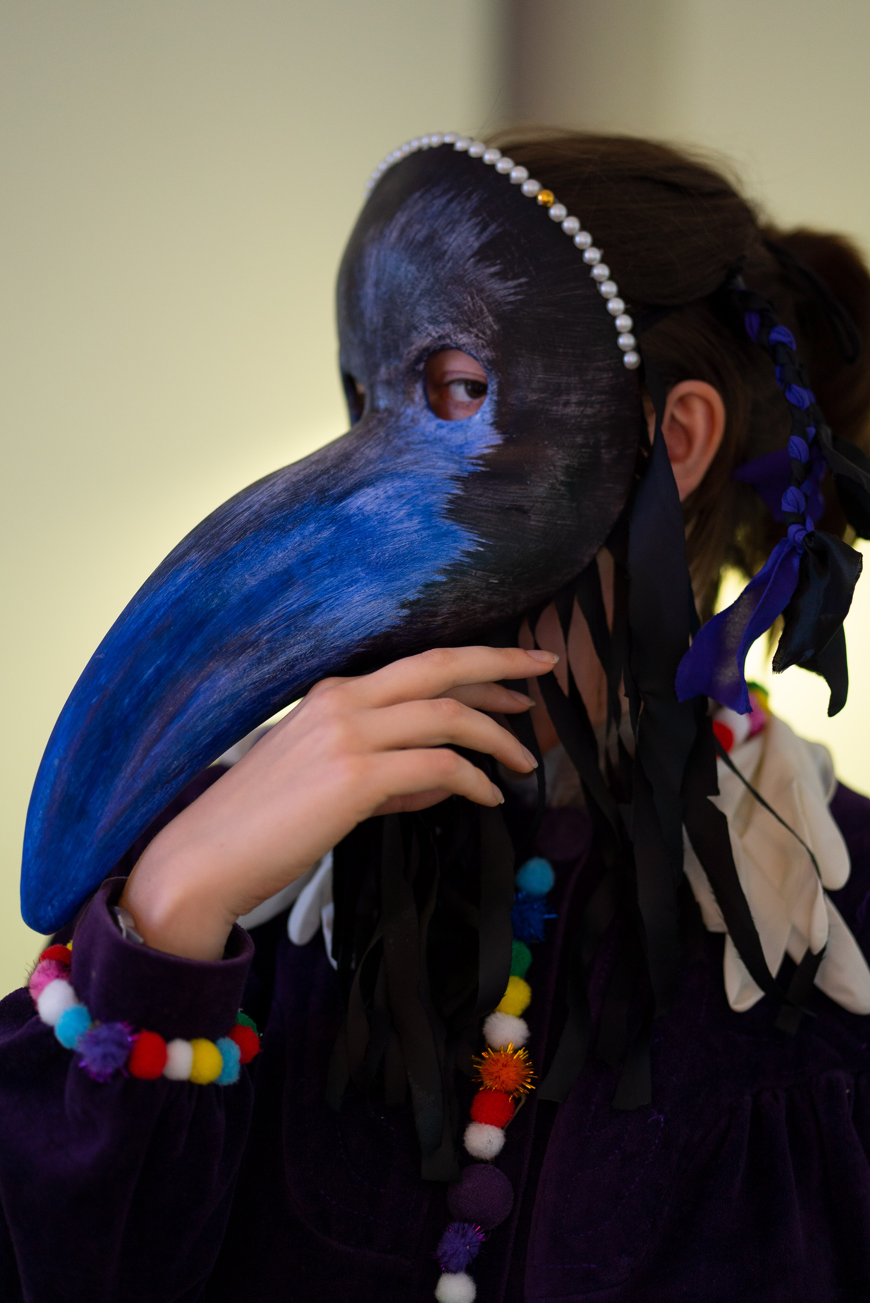 The photo is a close-up of a side profile of a person wearing a plague doctor mask. The mask is painted with black and blue paint, the upper edge of the mask is decorated with white pearls. The person is wearing a purple velvet coat decorated with colorful fabric balls on the cuffs and button closures. They hold their right hand under the beak of the mask. The eye visible under the mask looks directly into the camera.