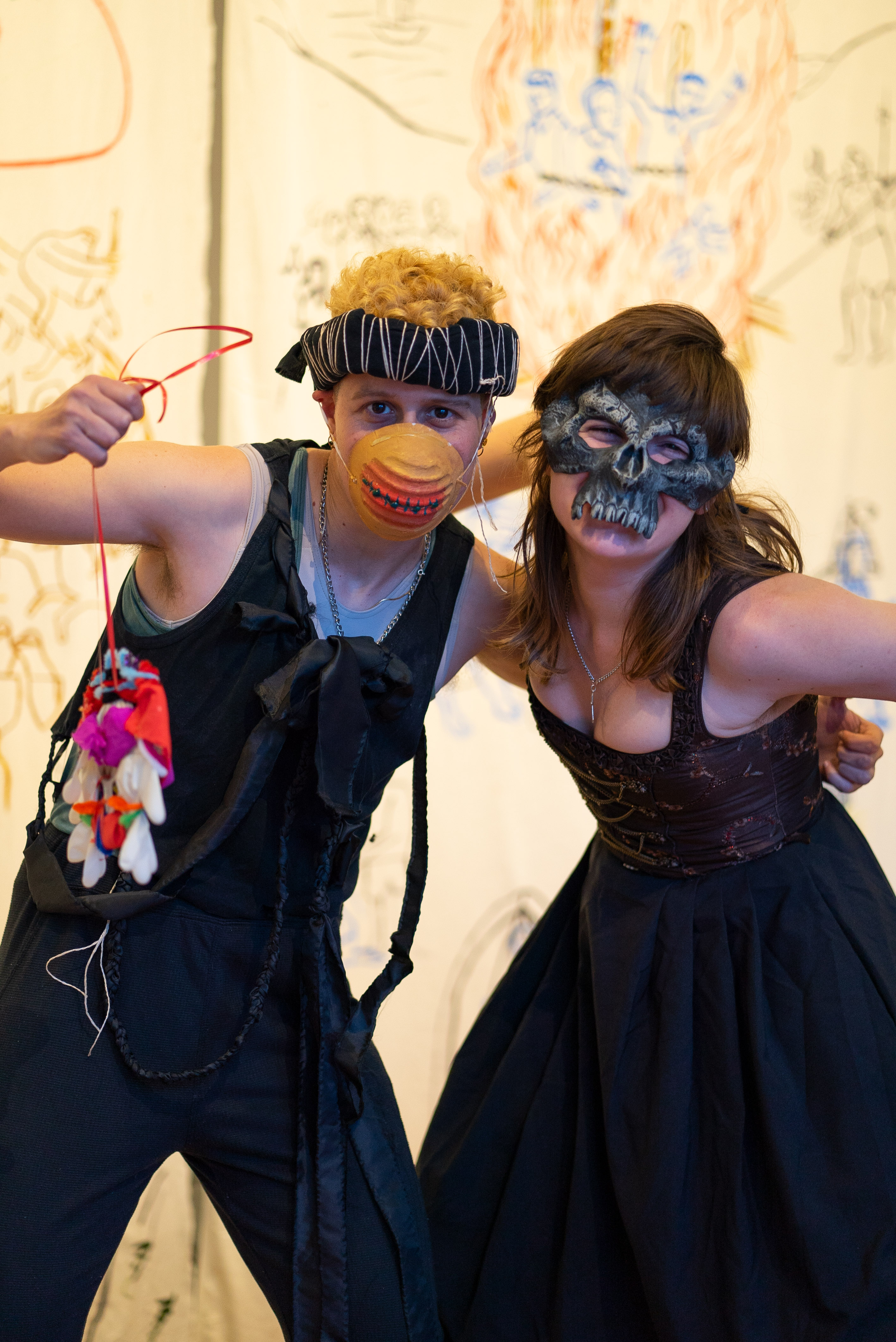 The photo shows two people in costumes posing on a stage. They have one arm around each other. The person on the left wears a patterned fabric ring as headgear, a painted protective mask that looks like a sewn up mouth, a black muscle shirt and black trousers. In their right hand they hold a self-made medallion in the air. The right person is wearing a skull mask and a dress that accentuates their cleavage. In the background hang banners made of antique white fabric with colourful medieval figurative paintings.