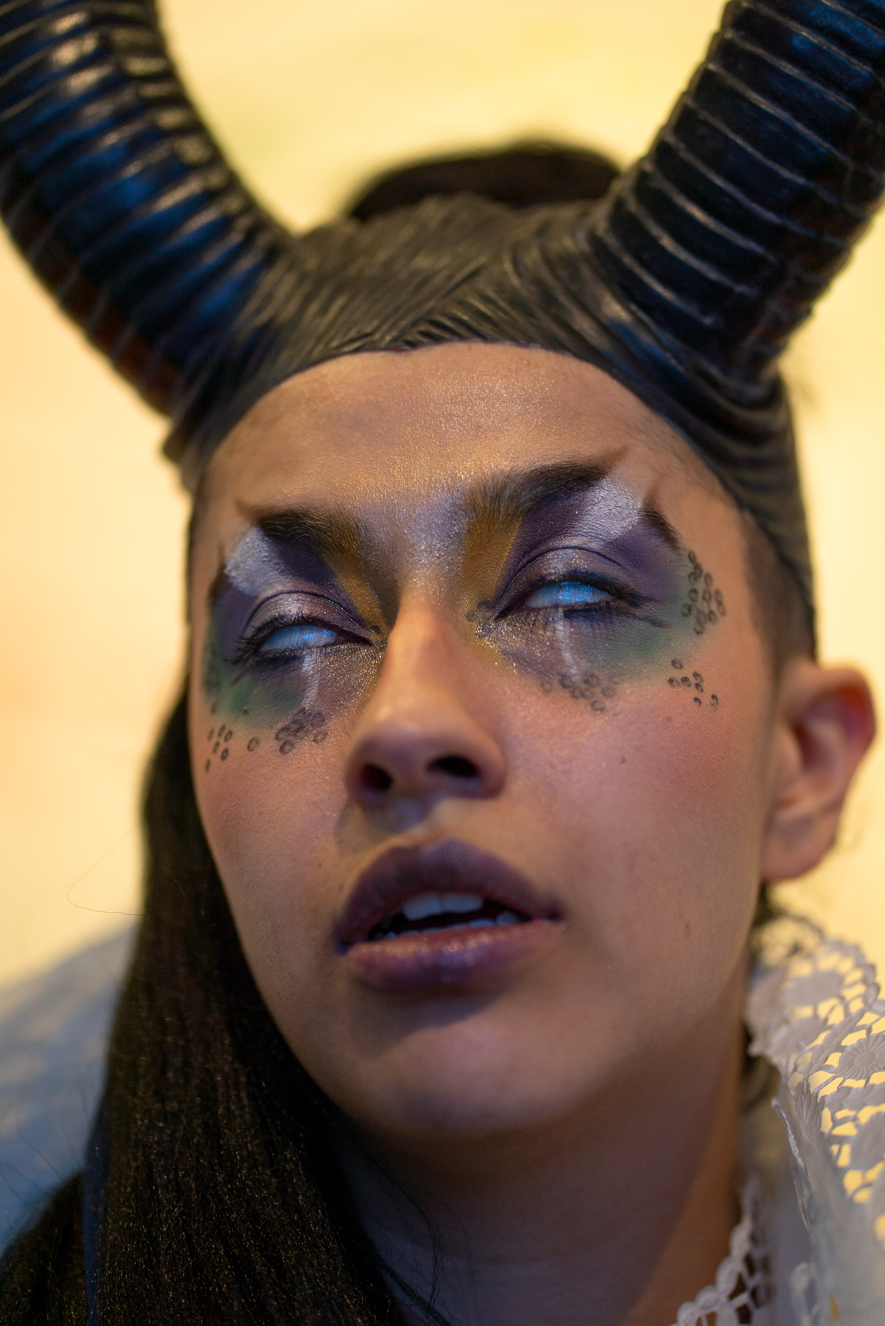The photo is a close-up of a person with two plastic horns as headgear and imaginative eye make-up in purple, green, white and black with glitter. They have opened their mouth slightly. Their eyeballs are turned upwards and slightly opened, so that only the white of the eye is visible.
