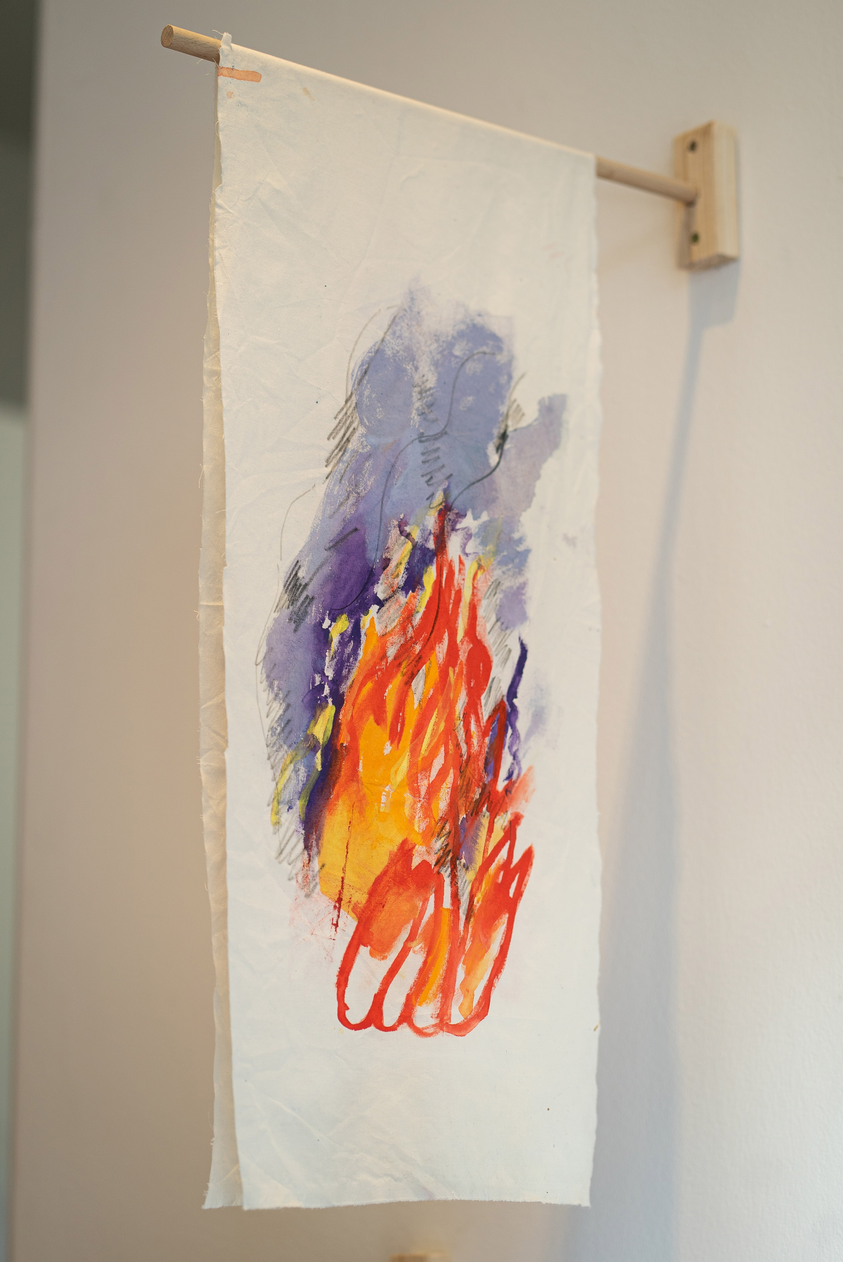 "The photo shows a piece of rectangular antique white fabric hanging from a wooden pole on the wall. It resembles a coat of arms. A fire is painted on the fabric with bright red, orange and purple colors. The coat of arms is part of the stage installation by Irene Fernandez Arcas for the exhibition ""Burlungis"" at Galerie im Turm in Berlin."
