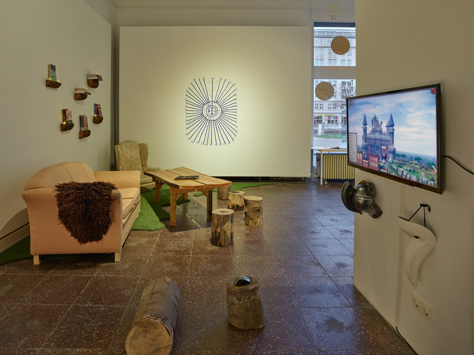 "The photo is an exhibition view of the show ""Burlungis"" in Galerie im Turm in Berlin. On the left side of the space next to the wall there is an old pink couch, behind it in the corner a beige armchair, next to the couch a table whose table top was made from a tree trunk with bark. The furniture stands on a piece of artificial grass in a curvy shape. The rest of the floor is made of stone-gray tiles. Cut tree trunks are scattered around the table as seating. In the middle on the back wall is painted a blue color and an oval shape a lunar calendar. On the right side of the picture there is a monitor on the wall of a column. A lock can be seen on the monitor in 3D. The image section belongs to a computer game. Two objects decoratively hang under the monitor. The left object is a silver armor made of plastic, the right object is a white plague doctor mask."