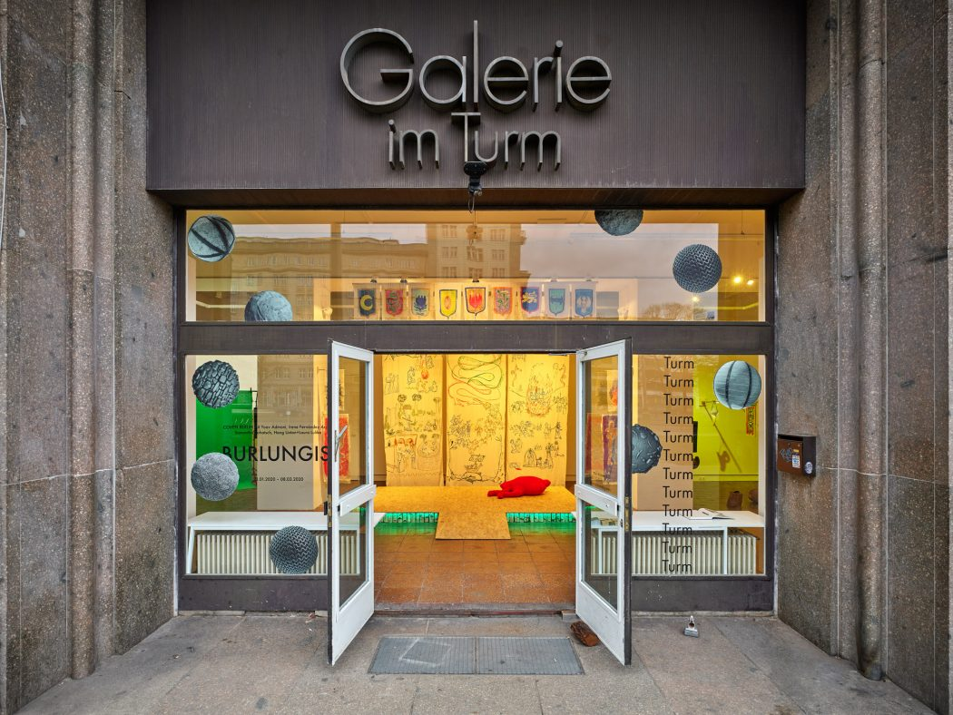 The photo shows an exhibition view of Burlungis from outside. The double doors of the gallery space Galerie im Turm are wide open. Above, the gallery name is lettered in metal on the stone wall. The stage installation by Irene Fernandez Arcas is visible inside.