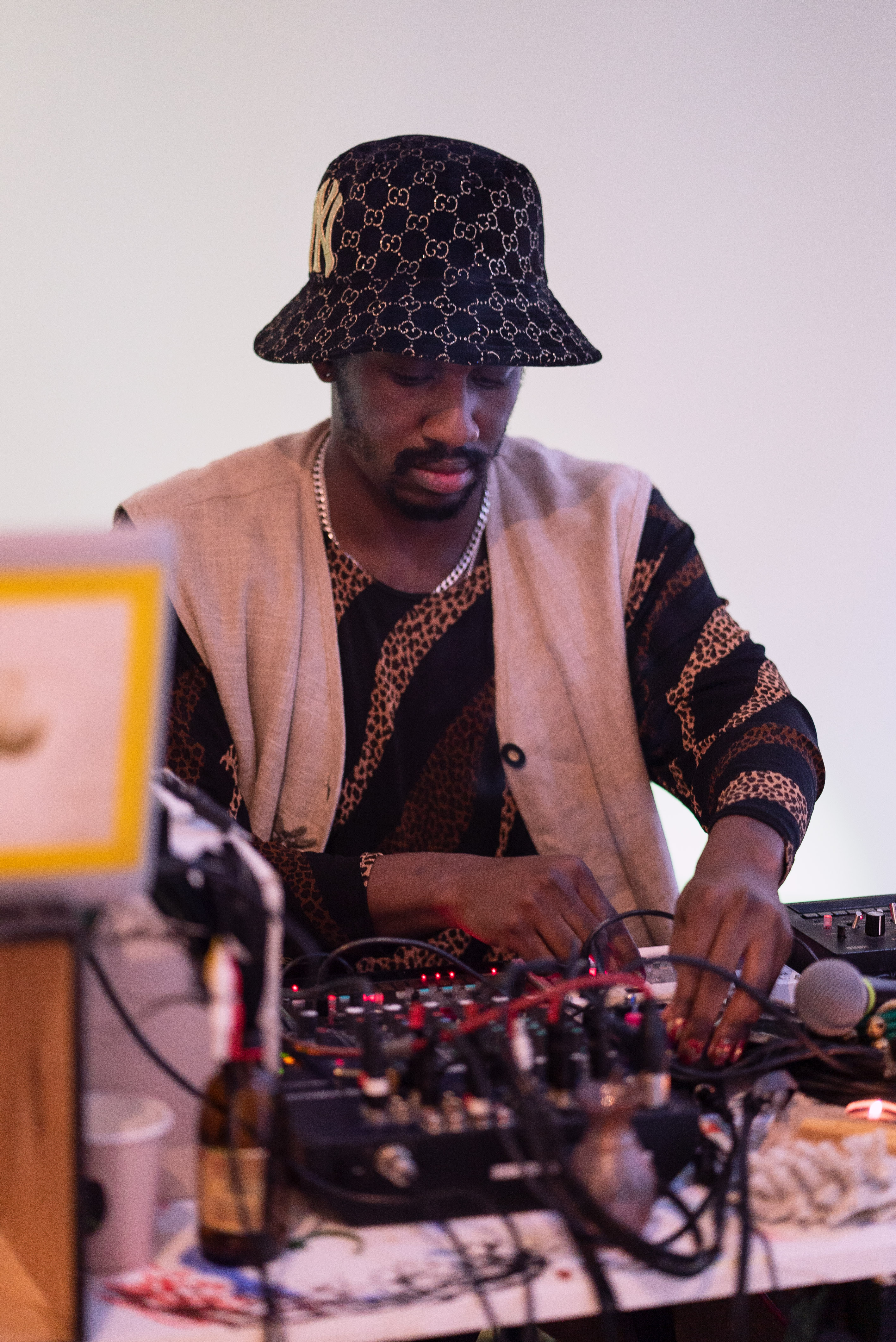 The photo is a medium shot of a person from the front sitting at a DJ table. They are wearing a hat and a traditional vest. In the foreground and out of focus we see equipment, cables and a microphone. The person operates equipment for DJing.